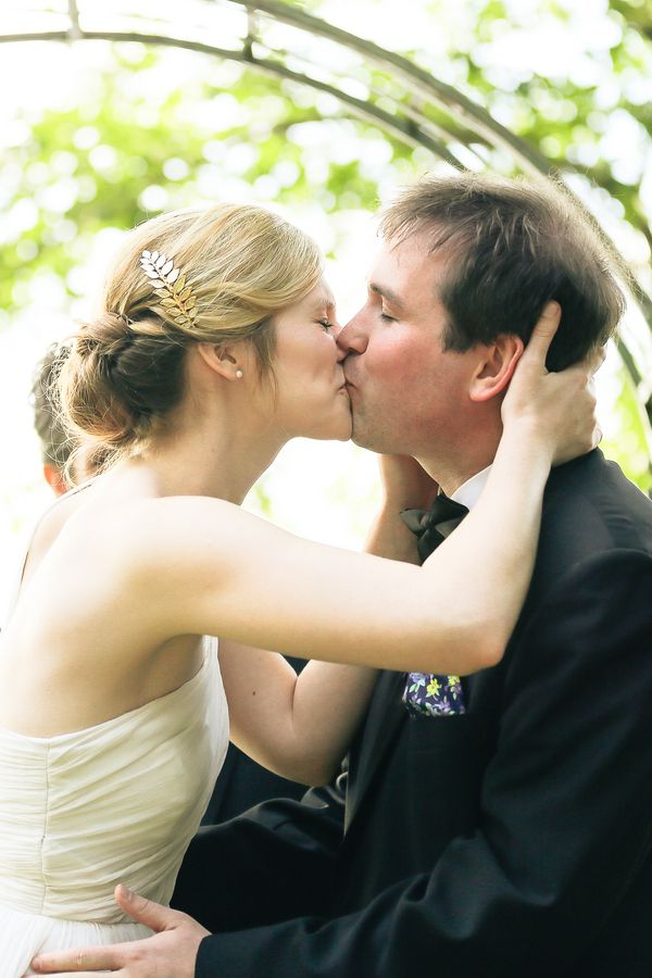 Bride kisses groom wearing soft low updo with gold leaf barrette