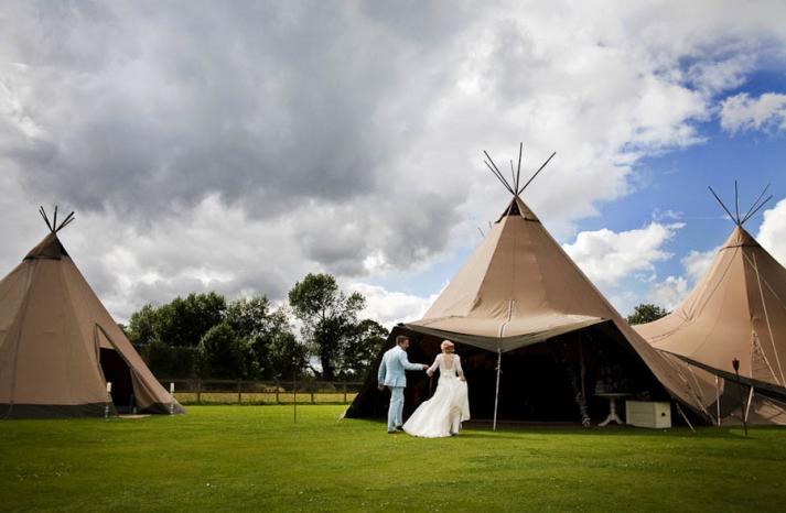 Bride and groom walk towards teepee during outdoor wedding