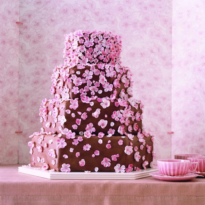 Chocolate wedding cake adorned with pink ediible cherry blossoms