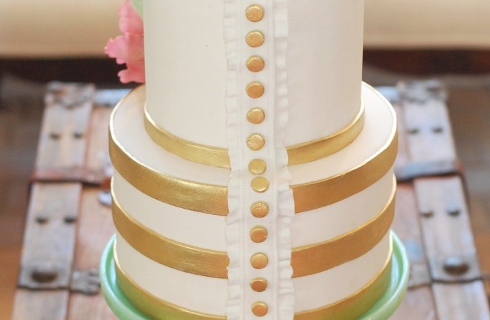 Ivory wedding cake with gold buttons and bands