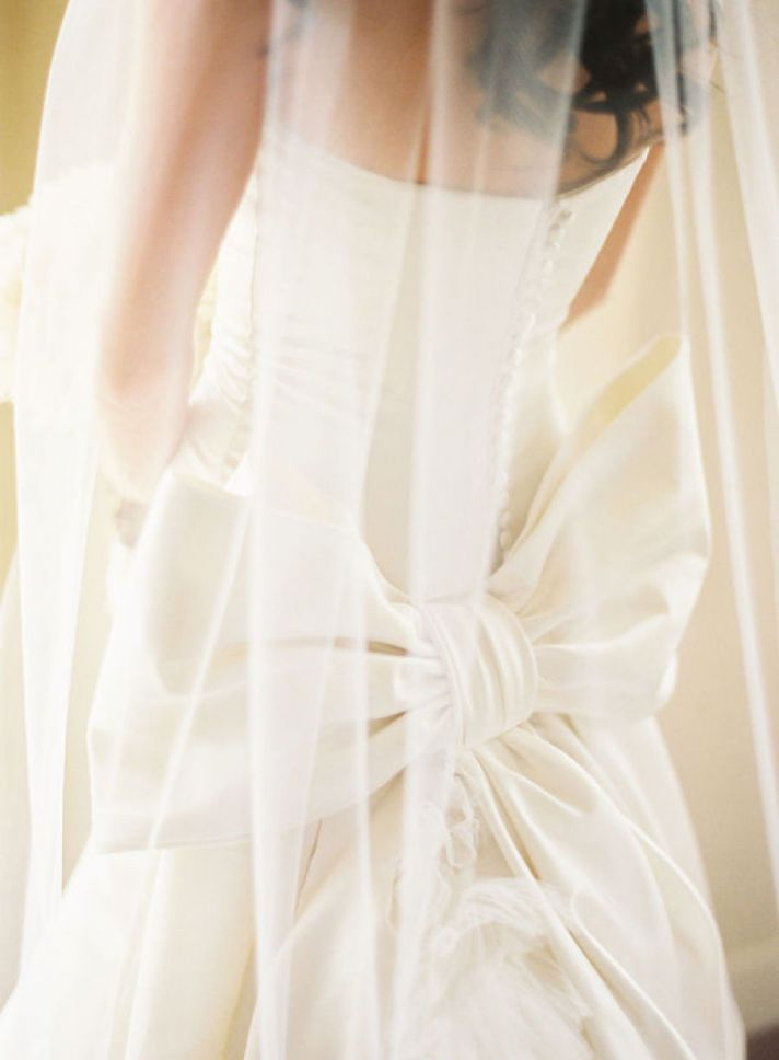 Bride wears Vera Wang wedding dress with covered buttons down back