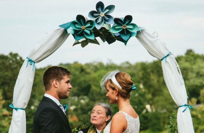 Origami flower adorned wedding ceremony arbor