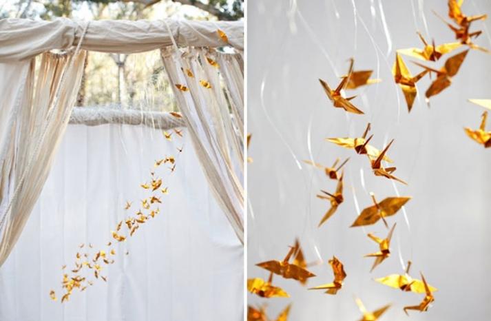 gold origami cranes decorate outdoor wedding arbor