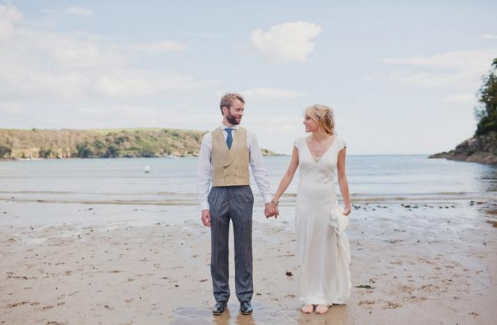 Groom wears khaki vest and striped navy pants for seaside wedding
