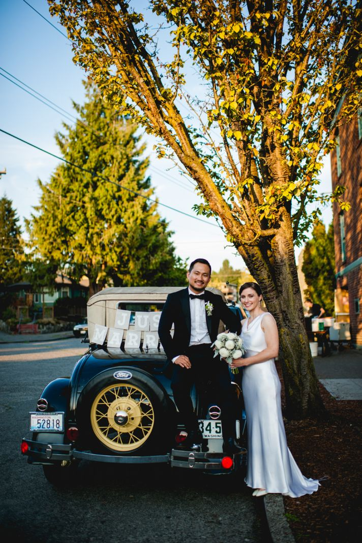 Bride and groom pose in front of vintage wedding ride