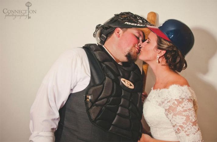 Bride and groom kiss wearing baseball gear