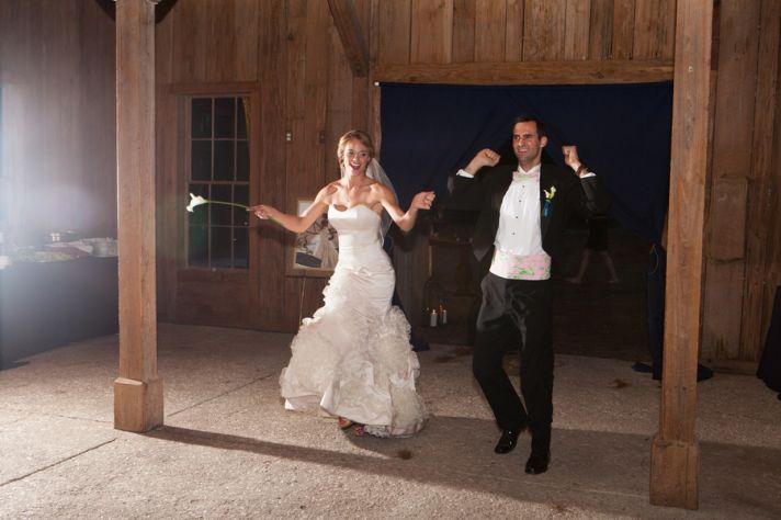Bride and groom make fun entrance into rustic reception venue