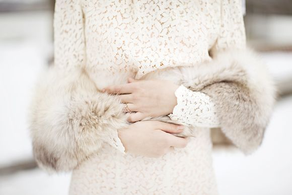 winter bride wears lace coat with fur stole