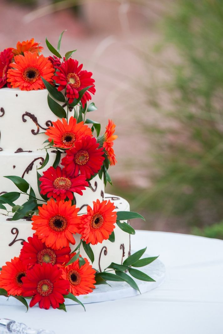 Birght orange and red blooms on white wedding cake