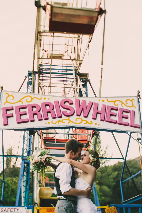 Kiss In Front of Ferris Wheel Wedding Photo